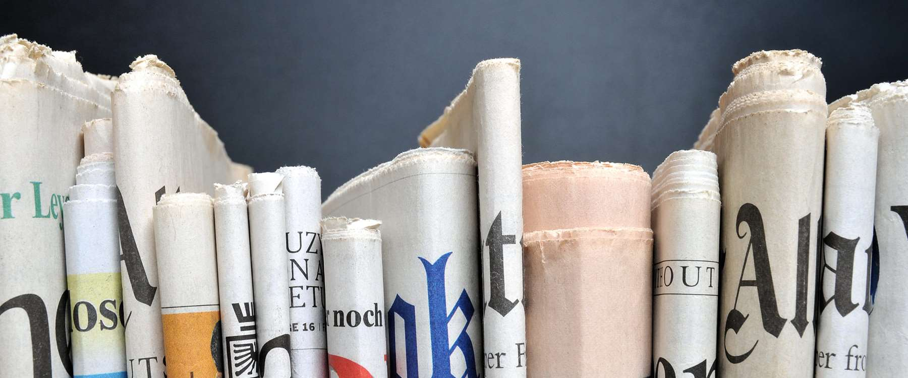 close up of news papers on book shelf